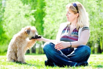 女性の手に前足で触れる犬