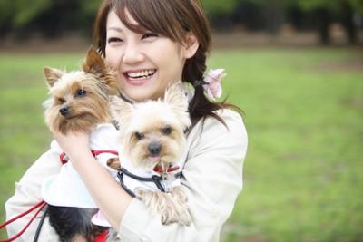 2匹の犬を抱っこする女性