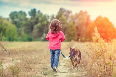 小さな女の子とお散歩中の犬の後姿