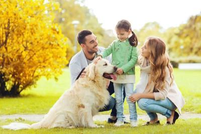 笑顔の家族と座るゴールデンレトリバー