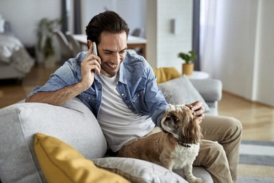 電話をしている男性と犬