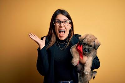 犬を抱えて騒ぐ女性