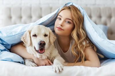 ベッドの中の犬と女性