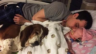 ベットで寝るパパと赤ちゃんと犬