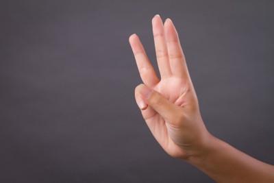 3本の指を立てている手