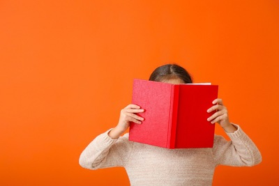開いた本で顔を隠している女の子