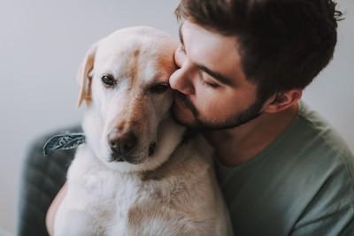 愛犬をバックハグするひげの男性