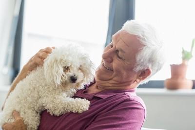 小型犬を抱く年配の男性