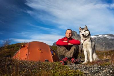 飼い主と一緒にキャンプをするシベリアンハスキー