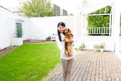 芝生のある庭と犬を抱く女性