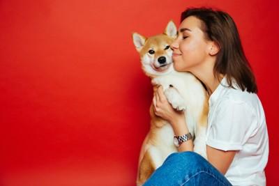 女性に抱きしめられる柴犬