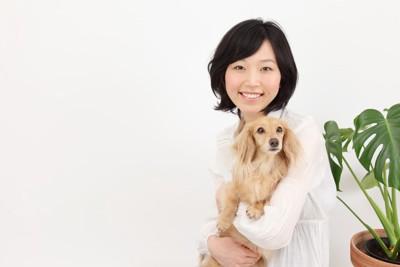 抱っこされる犬と女性