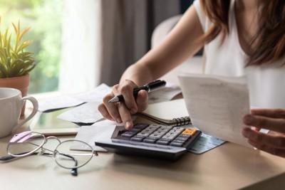 テーブル上、電卓で計算する女性