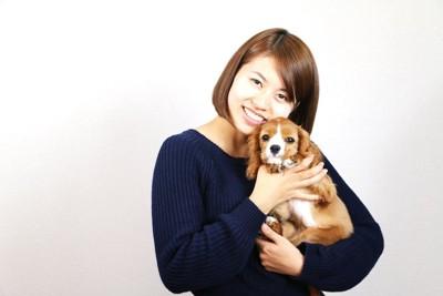 子犬を抱き上げる女性
