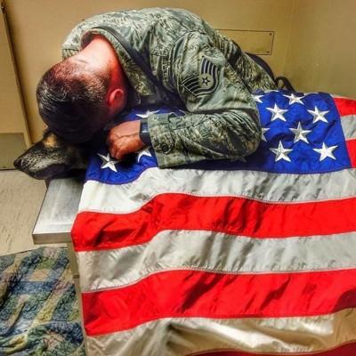 国旗をまとった犬に顔をつける男性