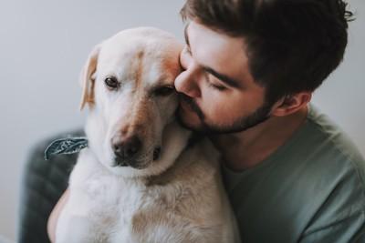 犬に後ろから寄り添う男性