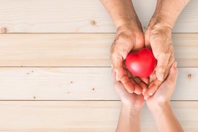 高齢者の手をつつむ人の手