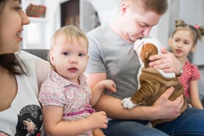 赤ちゃんを抱く母親と子犬を抱く父親