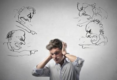 イラストの人に批判されて耳を塞ぐ男性