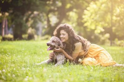 芝生の上に伏せる犬を撫でる女性