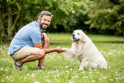 笑顔で握手する犬と男性