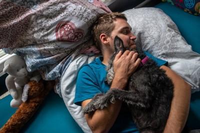 飼い主の男性の上に乗って眠る犬