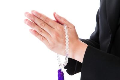 数珠を持って合掌している女性