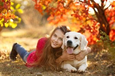 夕日に照らされる犬と女性