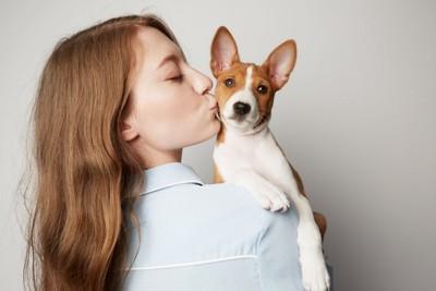 子犬を抱き上げるキスする女性