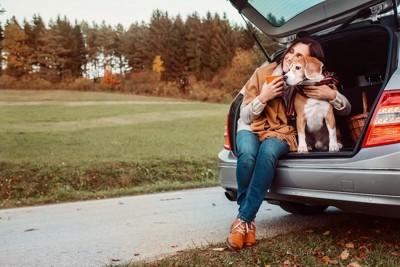 車のトランクに座る女性と犬