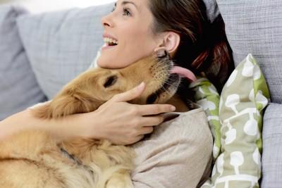 女性に抱きしめられて舌を出すゴールデンレトリバー