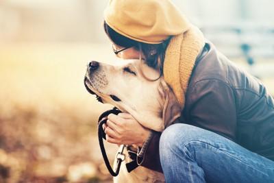 目を閉じた犬を後ろから抱きしめる女性
