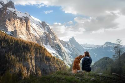 大自然の中で寄り添う犬と女性