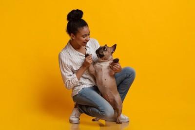女性笑っている 犬の前足を持ちたっちしているポーズ