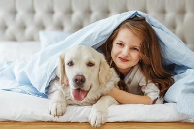 ベッドの上で飼い主さんと一緒にいる犬
