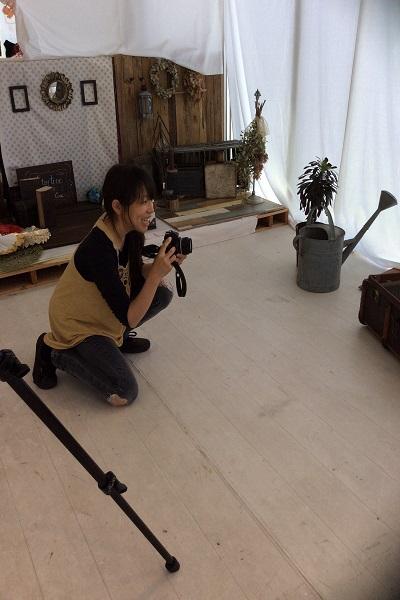 スタジオ内 女性 しゃがんでカメラを構えている