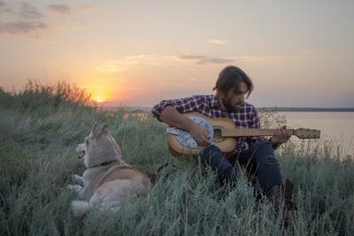 草原でギターを弾く男性とくつろぐ犬
