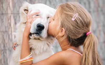 女の子に無理やりキスをされている白い犬