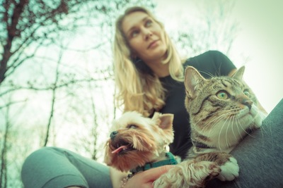 犬と猫を膝に乗せる女性