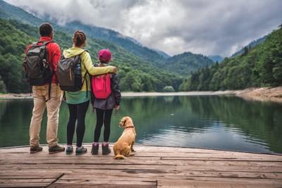 水辺に立つリュックを背負った家族と犬