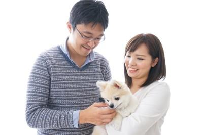 犬を抱く女性と笑顔で撫でる男性