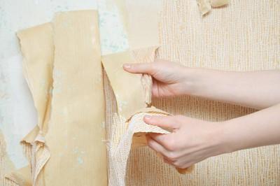 剥がれた壁紙を触る女性の手