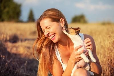 散歩の途中にしゃがんだ女性を舐める犬
