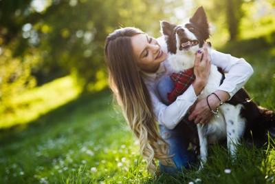 芝生の上で犬を抱きしめる女性