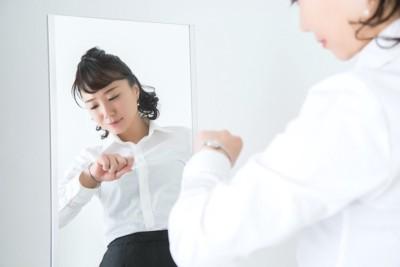 時計を見ながら出かける準備をする女性