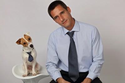 首をかしげるネクタイをした男性と犬