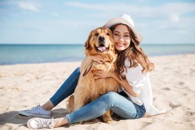 砂浜に座る女性とゴールデン