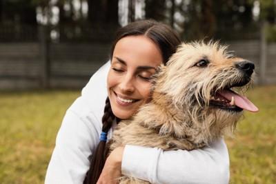 女性にハグされている犬