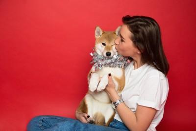 柴犬を抱いてキスをする女性