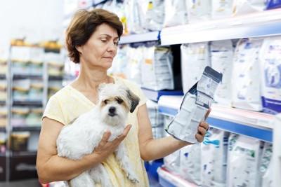 お店で犬を抱いてフードを選ぶ女性